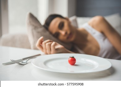 Suffering from anorexia. Little tomato on the plate in the foreground, depressed girl lying in the background