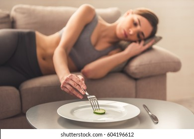 Suffering from anorexia. Slice of cucumber on the plate in the foreground, depressed girl lying in the background