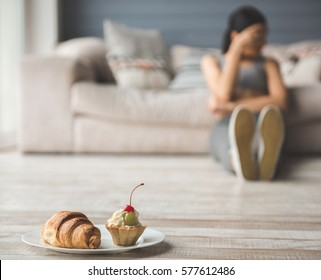 Suffering from anorexia. Sweet on the plate in the foreground, depressed girl sitting in the background
