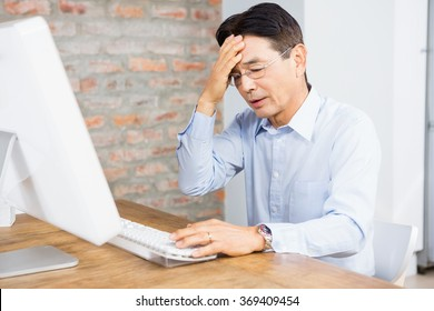 Suffering man with hand on face at home sitting in front of computer