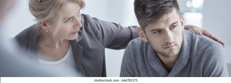 Suffering man with social phobia during psychotherapy with supporting  therapist