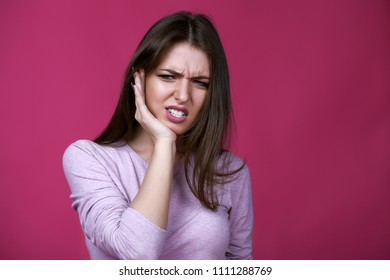 Suffering from toothache. Beautiful young woman suffering from toothache while standing against pink background