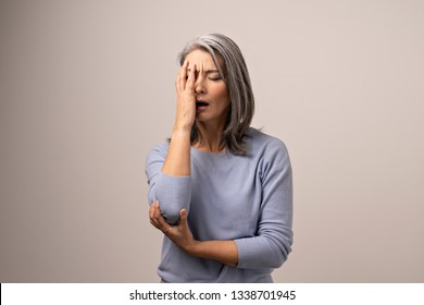Suffering Woman Covers Her One Side Of Face With A Hand. Middle-Aged Asian Woman In Distress Covering Her Face With Hand. Portrait.