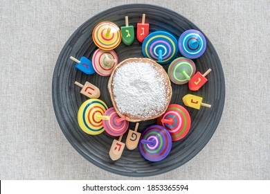 Sufganiya, spinning tops and wooden dreidels for Jewish holiday Hanukkah on dark plate over rustic background.