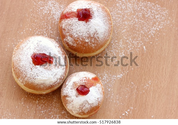 Sufganiyot traditional Jewish food for Chanukkah holiday on a wo