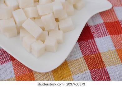 Sugacubes on white plate closeup.
