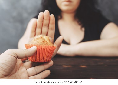Sugar addiction, healthy lifestyle, weight loss, dietary, healthcare and medical concept. Cropped portrait of overweight woman refusing muffin