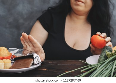Sugar addiction, healthy lifestyle, weight loss, dietary, healthcare and medical concept. Cropped portrait of overweight woman choosing healthy food refusing chocolate bar