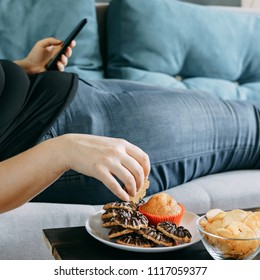 Sugar addiction, unhealthy lifestyle, weight gain, dietary, healthcare and medical concept. Cropped portrait of overweight woman laying on sofa eating sugary foods