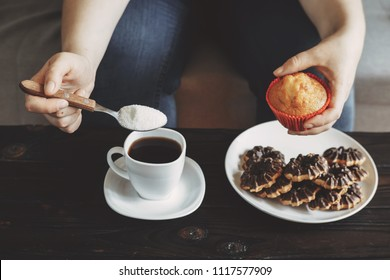 Sugar addiction, unhealthy lifestyle, weight gain, dietary, healthcare and medical concept. Cropped portrait of woman pouring sugar into coffee cup and eating sugary food