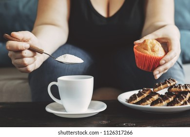 Sugar addiction, unhealthy lifestyle, weight gain, dietary, healthcare and medical concept. Woman pouring huge amount of sugar into coffee cup and eating sugary food, chocolate cookies, muffins