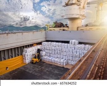 Sugar bags are loading in hold of bulk-vessel at industrial port, Forklift is handling and stacking sugar bags in hold of bulk-vessel.