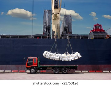 Sugar bags are loading in hold of bulk-vessel at industrial port,Pick up sugar bags from truck to  loading on board.