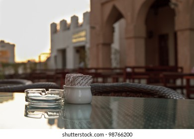 A sugar bowl and ashtray on a glass topped coffee table at the souk are ready for late afternoon visitors