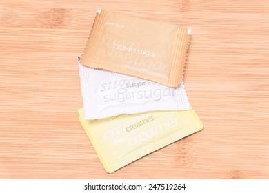 sugar, brown sugar, creamer on wood background