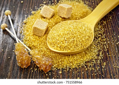 Sugar brown granulated in a spoon, cubes and crystal on a stick against a dark wooden board