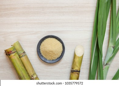 sugar cane and brown sugar on wooden table.