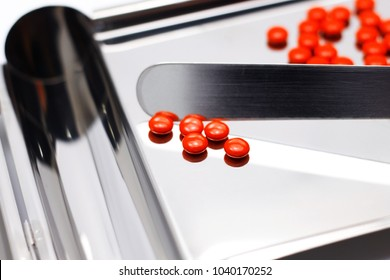 Sugar coated tablet pills on Stainless Steel counting tray with spatula for pharmacist in drugstore isolated on white. Colorful tablets related to Vitamin, NSAIDS, Steroids etc. Selective focus.