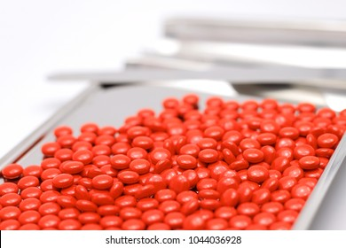 Sugar coated tablets on Stainless Steel counting tray spatula for pharmacist in isolated on white background with text copy space. Pills related to Vitamin B, NSAIDS, Steroids. Selective focus.