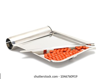 Sugar coated tablets on Stainless Steel counting tray for pharmacist in drugstore isolated on white background with text copy space. Pills related to Vitamin B, NSAIDS, Steroids.