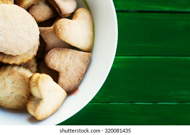 Sugar cookies on a plate on a green wooden background
