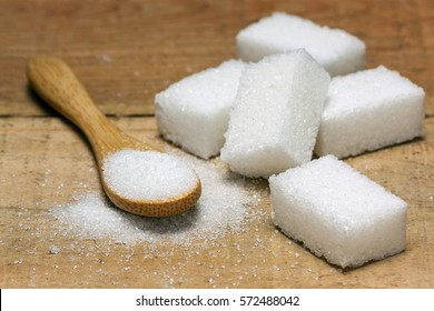 sugar cube in the spoon on wood background