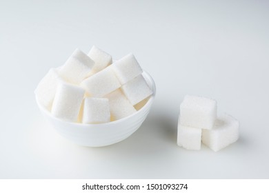 Sugar cubes in sugar bowl and near on white background