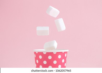 Sugar cubes falling into paper cup polka design against pastel pink background minimal creative concept.