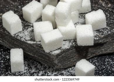 Sugar cubes and granulated sugar on black rock slate.