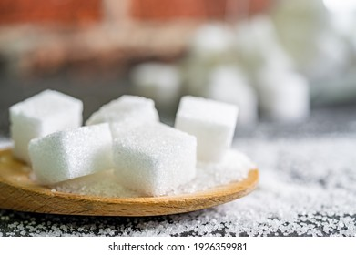 sugar cubes on black backround. Sugar is unhealthy nutrition and leads to obesity, diabetes, dental care