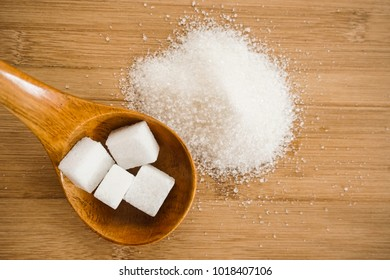 Sugar cubes and sugar sand on wooden background. Top view.