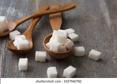 Sugar cubes in spoon on gray  background.