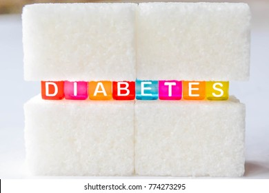 Sugar cubes with the word diabetes in between. Diet unhealty sweet addiction concept. Diabetes 2 concept suggesting no sugar consumption to improve health.