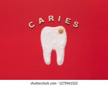 Sugar destroying tooth enamel and leading to caries. Tooth with decay made from white and brown sugar on red background, top view