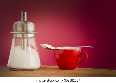 Sugar dispenser and coffee cup. Conceptual image of using too much sweetener and unhealthy eating and drinking.