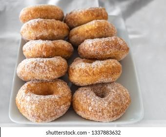 Sugar doughnuts on a white plate.