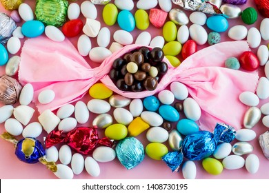 The Sugar Feast end of holy Ramadan,conceptual image with pink color paper bonbon shape candy on the pink ground.Colorful almond candies and chocolates designed around of bonbon.