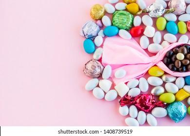 The Sugar Feast end of holy Ramadan,conceptual image with pink color paper bonbon shape candy and colorful almond candies on the pink ground.Left space for any text message.