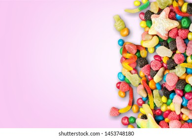The Sugar Feast end of holy Ramadan,conceptual image with pink color paper bonbon shape candy and colorful almond candies on the pink ground.Left space for any text message.          - Image