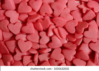Sugar hearts for cake decoration. Confectionery decoration close-up. Pink hearts. Abstract background.