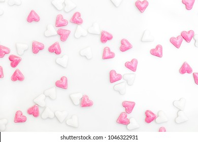 sugar hearts colored white and pink, spreading on white background, concept love card