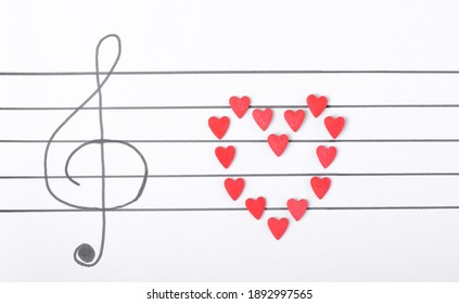 Sugar hearts making heart on the musical staff with treble clef. Music Valentine background. Creative composition