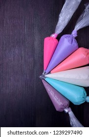 Sugar icing of different colors in pastry bags