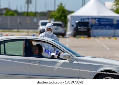 Sugar Land, Texas - April 16, 2020: Dressed in full protective gear a healthcare worker collects information from elderly couple sitting inside their car at the COVID-19 drive-through testing site