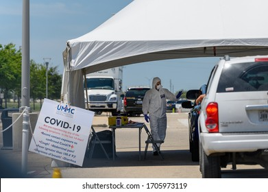 Sugar Land, Texas - April 16, 2020: Dressed in full protective gear a healthcare worker collects information from people sitting inside their car at the COVID-19 drive-through testing site