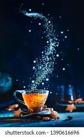 Sugar nebula creative food photo. Teacup with falling sugar forming Milky Way galaxy. Conceptual still life with
