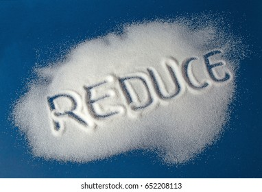 Sugar on a blue background with warning message REDUCE written on it. Health concept. Diabetes hazard