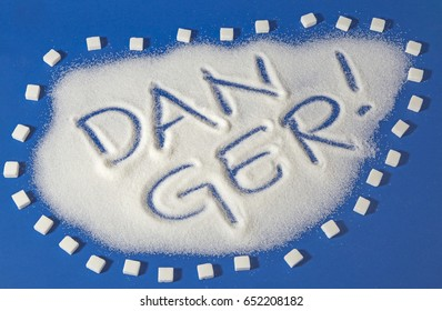 Sugar on a blue background with warning message DANGER written on it. Health concept. Diabetes hazard