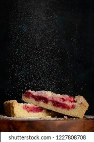 Sugar powder falling on two slices of homemade raspberry cake on black background.
