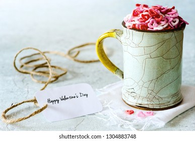Sugar shapes of hearts in a cup on delicate background, with greeting card